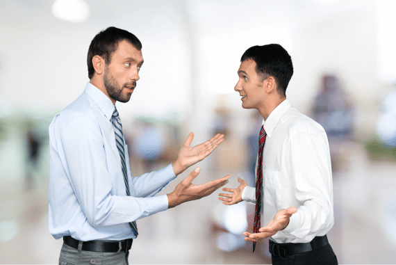 Two male colleagues arguing in the office