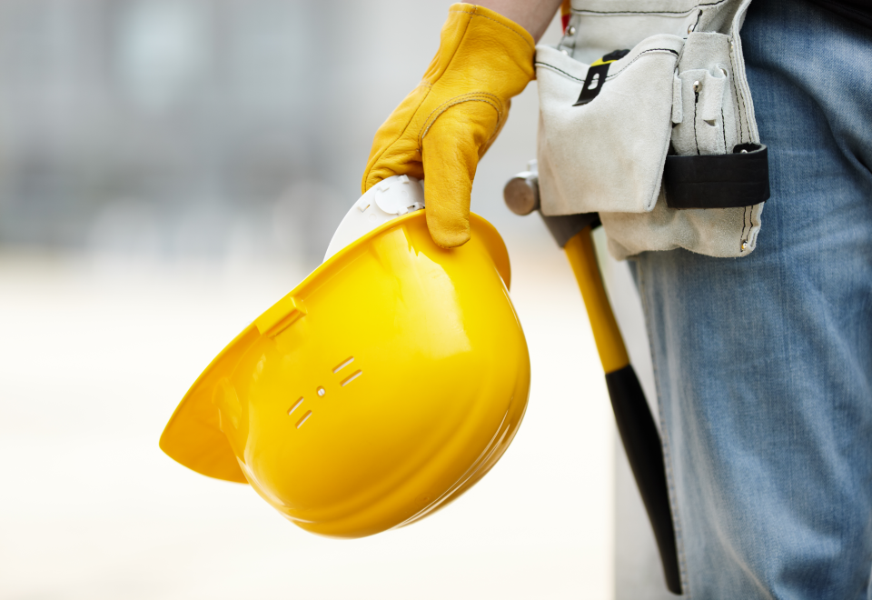 A construction worker with a tool belt holding a yellow protective hard hat