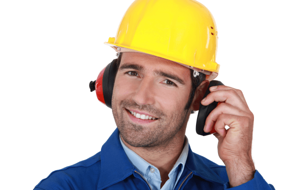 A worker smiling and wearing ear defenders