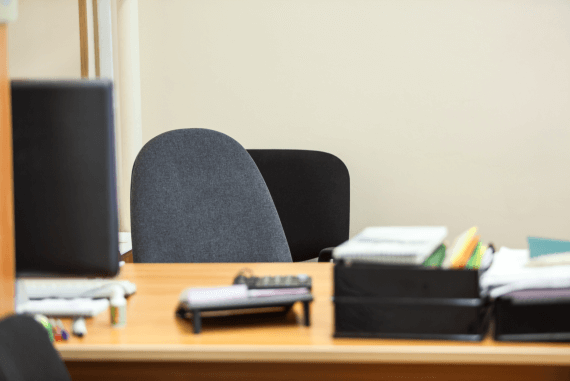 An empty office chair behind a desk