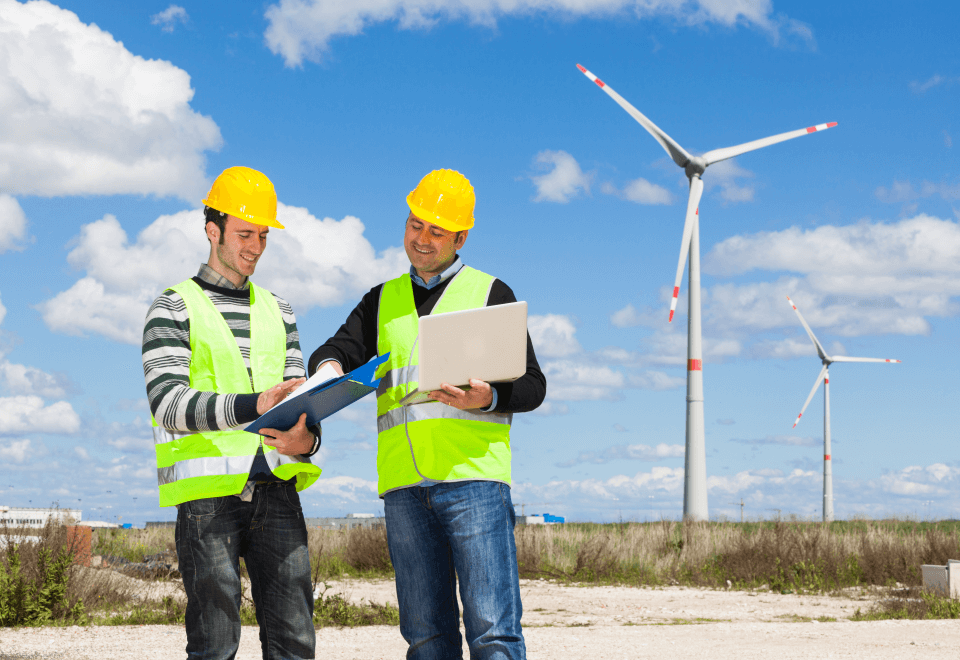 Two workers in safety gear stood next to a wind turbine with blue sky background