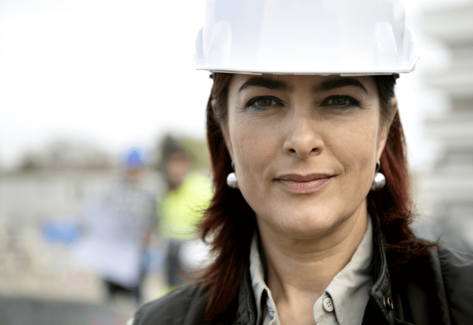 A female construction site manager wearing a protective hard hat