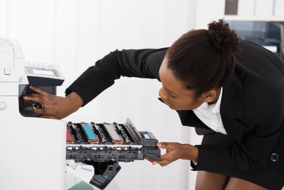 A woman fixing the photocopier in an office