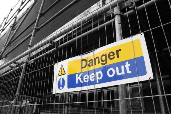 A keep out warning sign on a construction site metal fence