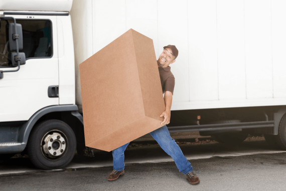 A delivery driver struggling to carry a very large box