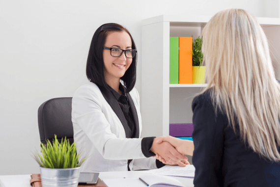 A female manager and female employee shaking hands