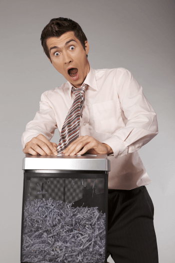 A man getting his tie entangled in a paper shredder