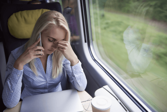 A female worker feeling stressed sat on a train