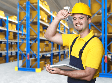 A warehouse worker smiling in a hard protective hat