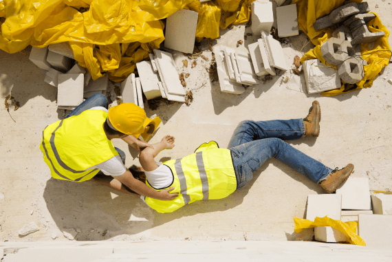 A construction worker lying on the ground after suffering an accident at work